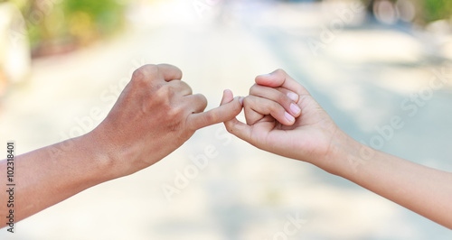 Fototapeta Parent and child hooking their fingers to make a promise
