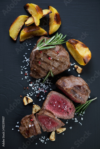 Rare beef filet mignon steak served with baked potato slices Canvas Print