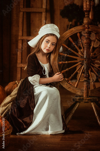 Fotografie, Obraz  little girl in the image of Cinderella sits near a spinning wheel from the hands , hip toning , happy childhood