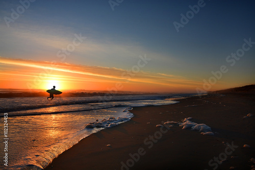 Photo  Man with surfboard on the beautiful sunrise beach, Outer Banks, North Carolina