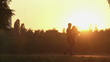 Happy married couple strolling in the park in golden sunset rays, magic hour