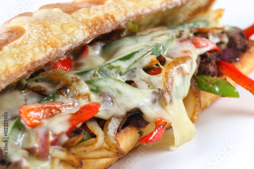 Staande foto Snack Tasty beef steak sandwich with onions, mushroom and melted provolone cheese in a ciabatta