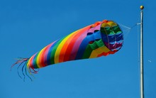 Bright Colorful Spinning Ocean Beach Windsock Kite.  Wind Blowing Thru Kite With Blue Sky Background.