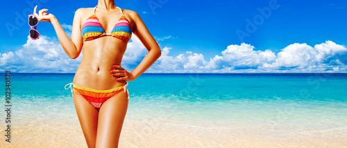 Obraz Beautiful woman body with colorful bikini. Holding sunglasses on the beach. Perfect shining skin.  - fototapety do salonu