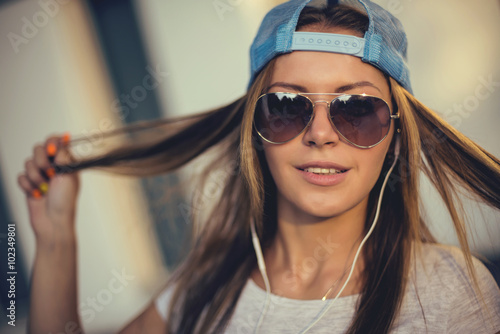 Papiers peints Magasin de musique Teenage girl listening to music. background of the street