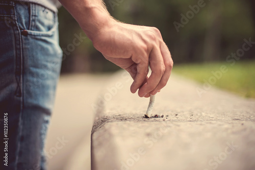 Photo Hand of a young man extinguish cigarette