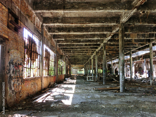 Crumbling abandoned factory warehouse with broken windows, landscape photo