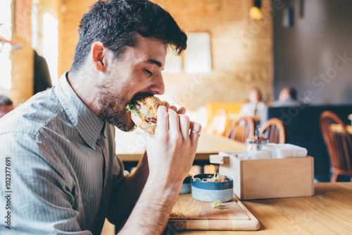 Photo  Man is eating in a restaurant and enjoying delicious food