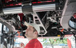 Young repairman ( farmer ) repairs tractor