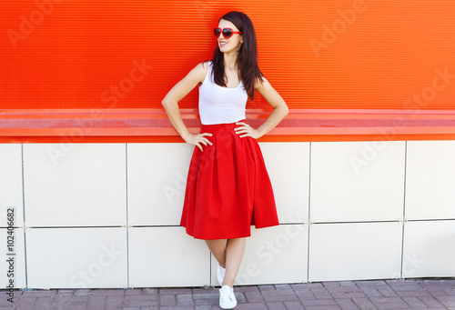 Fotografia Beautiful brunette woman wearing a sunglasses and red skirt in c