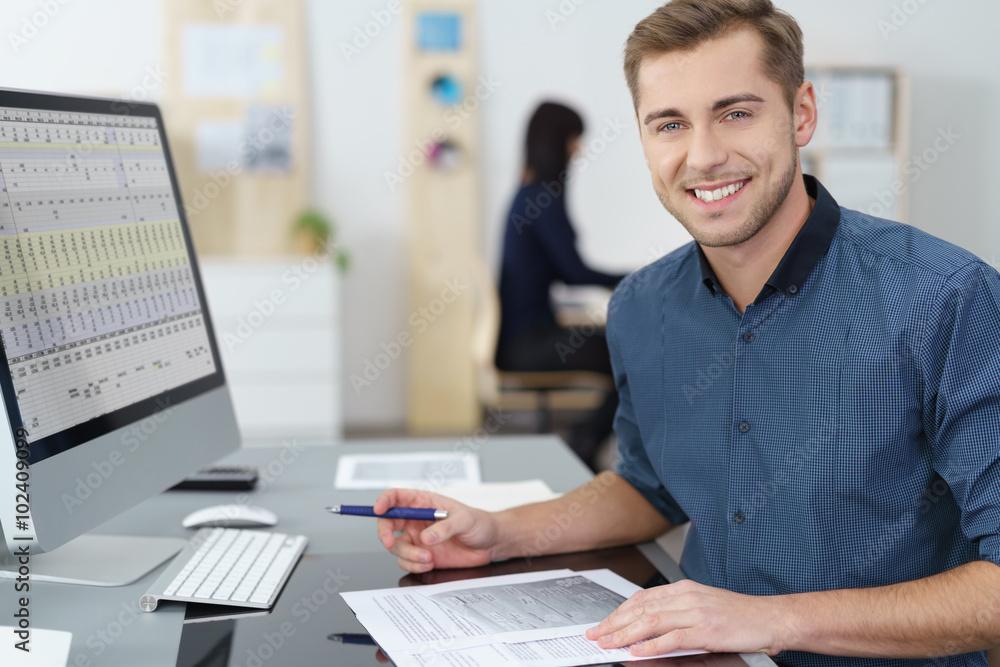 Fototapeta lächelnder mitarbeiter im büro arbeitet am pc