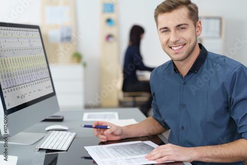 lächelnder mitarbeiter im büro arbeitet am pc
