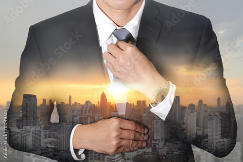 Businessman held necktie dress to look good and sunrise cityscape Poster