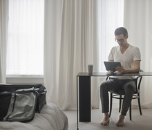 A Working Day. A Man Seated At A Laptop Computer, Working In A Hotel Bedroom.