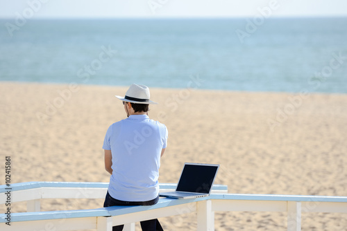 Fotografie, Obraz  Businessman working with laptop computer on the beach