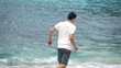 Young boy running on beach near sea, super slow motion 240fps