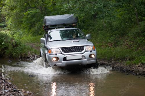 фотография  BOLSHOY KAMEN, RUSSIA - AUGUST 03, 2015: SUV is crossing a river