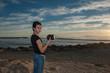 Teen photographer standing camera left at a Ventura beach.