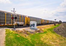 Wide Angle View Of Freight Train Passing At Railroad Grade Crossing With Signal