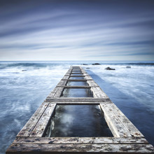 Wooden Pier Or Jetty On A Blue Ocean. Long Exposure