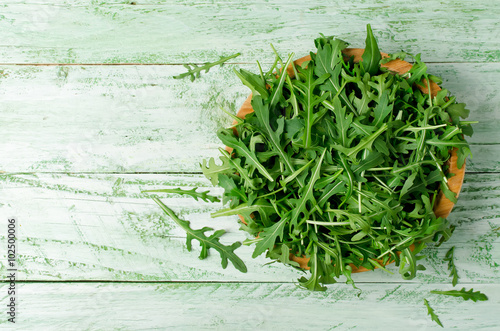 Photo Fresh green arugula in bowl on wooden table