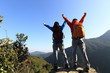 two successful backpacker open arms at mountain peak