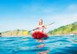 Woman exploring calm tropical bay by kayak.
