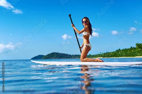 Plakat Rekreacyjne sporty wodne. Zdrowy szczęśliwy sprawny kobieta z seksownym ciałem wiosłowaniu, klęcząc na Stand Up Paddle, Surf Board In Sea. Wakacje letnie Wakacje podróżnicze. Aktywny styl życia. Spędzania wolnego czasu. Hobby