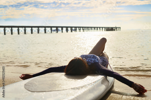 Summer Relaxation. Healthy Happy Woman With Fit Body Relaxing On Beach, Lying On SUP, Surf Board Near Sea ( Ocean, Water ). Holidays Travel Vacation. Lifestyle, Freedom, Wellness, Happiness Concept.