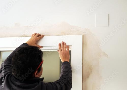 Carpintero coloca el embellecedor de una puerta corredera blanca Canvas Print