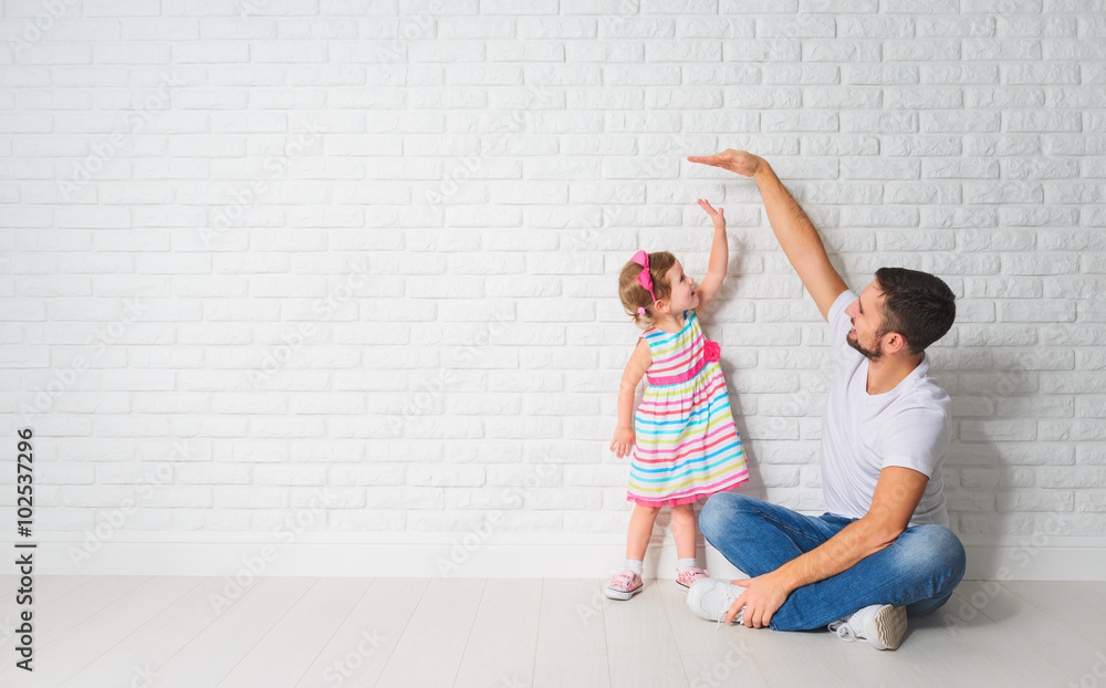 Fototapety, obrazy: concept. Dad measures growth of her child daughter at a wall