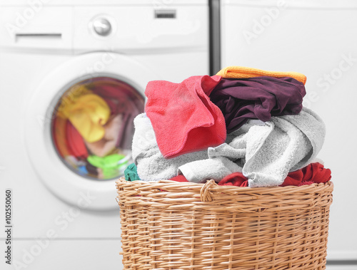 Fototapeta Basket with laundry and washing machine.