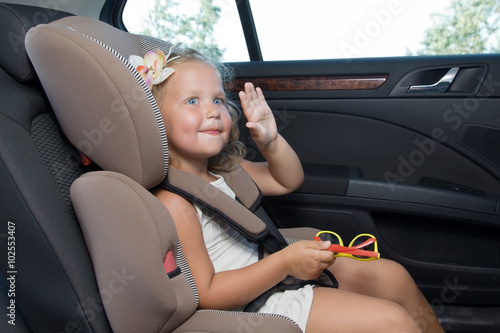 Little girl waves her hand sitting in car seat - Buy this stock ...
