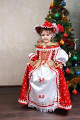 little girl in carnival costume near Christmas tree