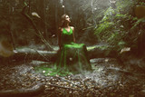 Woman wears a green dress in the forest