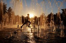 Boy Running Through A Fountain