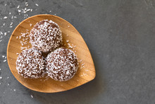 Coconut Rum Balls On Small Wooden Plate, Photographed Overhead Om Slate With Natural Light (Selective Focus, Focus On The Top Of The Balls)