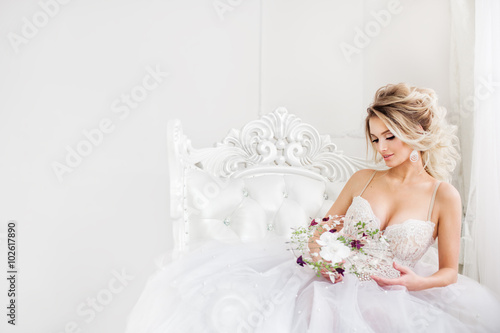 Stampa su Tela Young  bride is sitting in white armchair