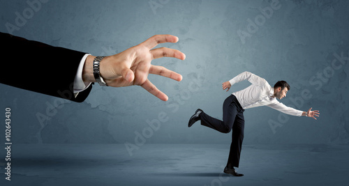 Photo Business man running away from a huge hand concept