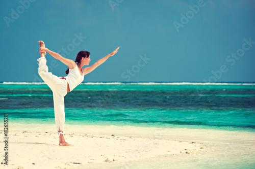 Stampe  Slim girl  making yoga on the sea sand