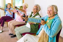 Cheerful Senior Women Exercising Their Arms.
