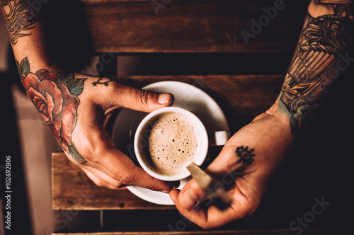 Elevated view of man with tattoo holding a cup of Coffee