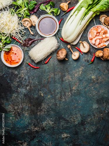Foto  Asiatische Küche Zutaten: Reisnudeln, pok choy, Soßen, Garnelen, Chili und Shiitake-Pilze auf dunklem Hintergrund, Ansicht von oben, Platz für Text