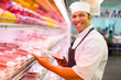 canvas print picture - mid age butcher organizing meat products