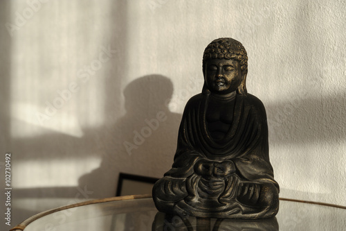 Fototapety, obrazy: Buddha statuette on the table.