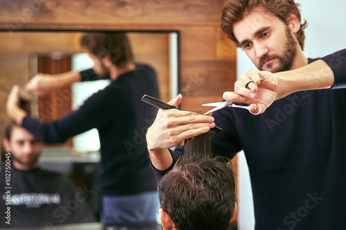 mata magnetyczna barber cutting hair with scissors. back view of man in barber shop.