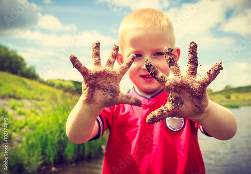 Photo  Child playing outdoor showing dirty muddy hands.