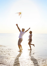 Happy Young Couple With Flying A Kite On The Beach