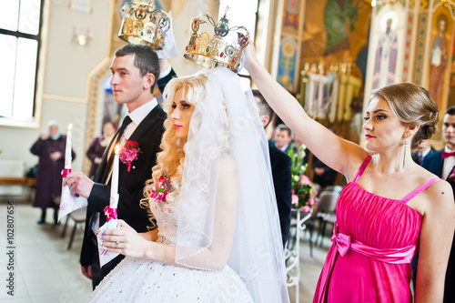 Bridesmaid holding crown on had of newlyweds at churh Tapéta, Fotótapéta