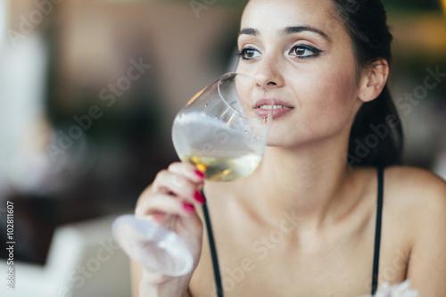 Foto  Attractive woman tasting white wine